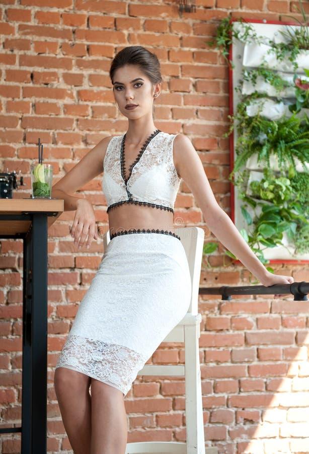 Μοντέρνη ελκυστική κυρία με το άσπρο φόρεμα που στέκεται κοντά σε έναν πίνακα εστιατορίων που έχει ένα ποτό κοντή γυναίκα τριχώμα στοκ φωτογραφία με δικαίωμα ελεύθερης χρήσης