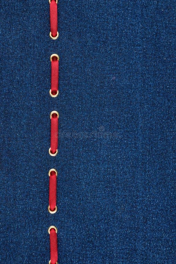 Μοντέρνη κορδέλλα σατέν υποβάθρου κόκκινη που παρεμβάλλεται στο τζιν στοκ εικόνες με δικαίωμα ελεύθερης χρήσης