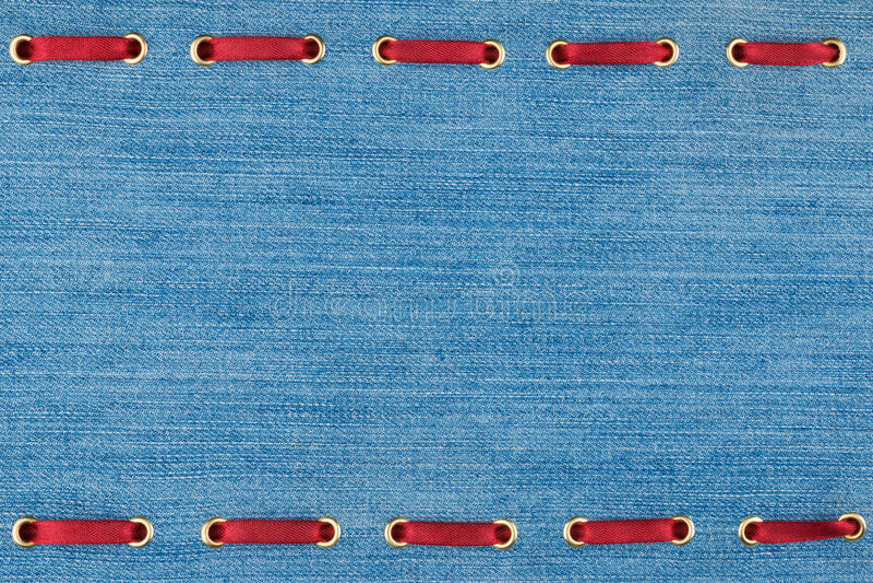 Μοντέρνη κορδέλλα σατέν υποβάθρου κόκκινη που παρεμβάλλεται στο τζιν στοκ εικόνες