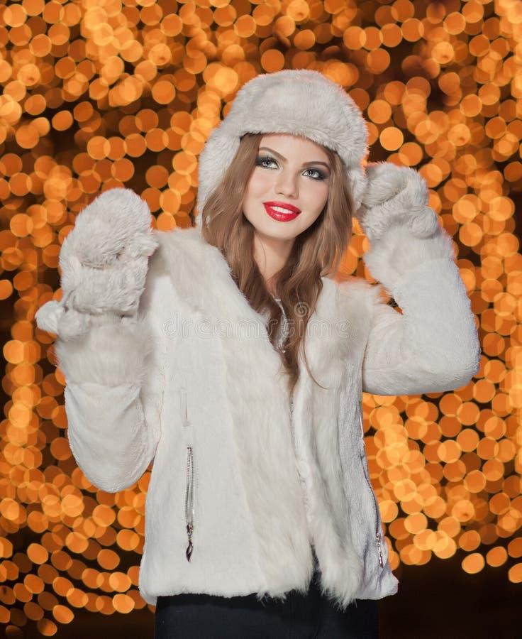 Μοντέρνη κυρία που φορούν την άσπρη γούνα ΚΑΠ και παλτό υπαίθριο με τα φωτεινά φω'τα Χριστουγέννων στοκ εικόνες