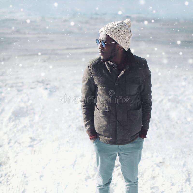 Μοντέρνη νέα αφρικανική φθορά ατόμων πορτρέτου χειμερινής μόδας γυαλιά ηλίου, πλεκτά καπέλο και σακάκι πέρα από το χιόνι στοκ φωτογραφία με δικαίωμα ελεύθερης χρήσης