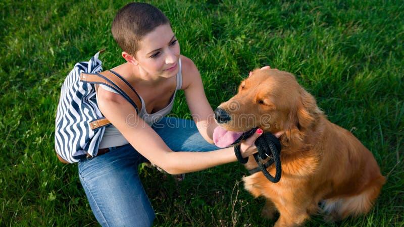 Μοντέρνη νέα γυναίκα και χρυσό retriever σκυλιών κατοικίδιων ζώων της στοκ εικόνες