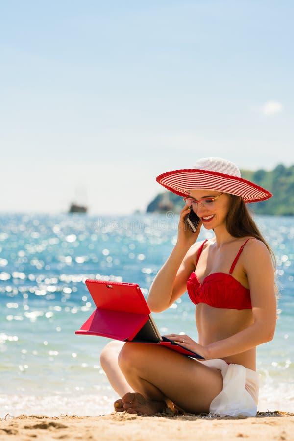 Μοντέρνη νέα γυναίκα που μιλά στο κινητό τηλέφωνο στην παραλία στοκ εικόνες
