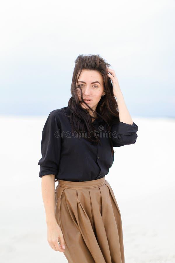 Μοντέρνη νέα γυναίκα που στέκεται στο χειμερινό μονοφωνικό υπόβαθρο και που φορά το μαύρο πουκάμισο με τη φούστα στοκ εικόνες
