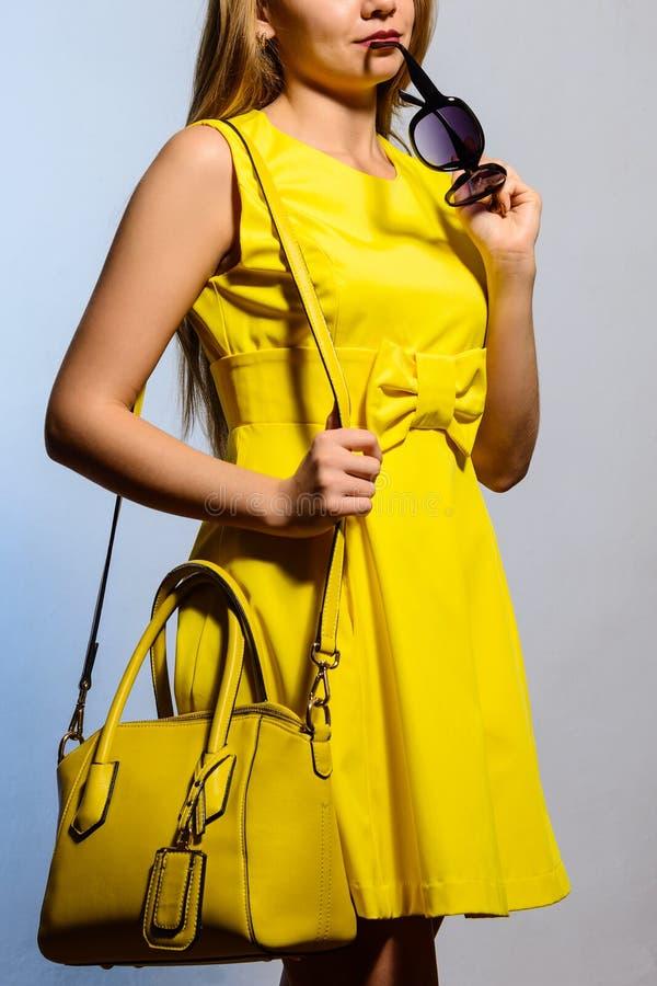 Μοντέρνη νέα γυναίκα στο κίτρινο φόρεμα με την τσάντα και τα γυαλιά ηλίου στοκ φωτογραφίες
