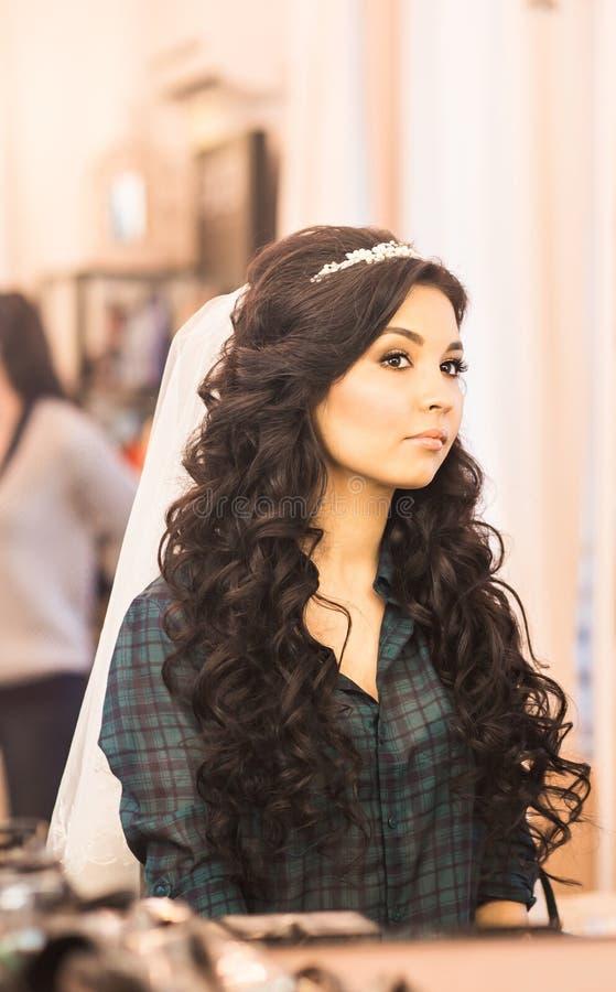 Μοντέρνη πανέμορφη νύφη που παίρνει makeup στην αίθουσα ομορφιάς πολυτέλειας με τους μεγάλους καθρέφτες και το φως στοκ φωτογραφία με δικαίωμα ελεύθερης χρήσης