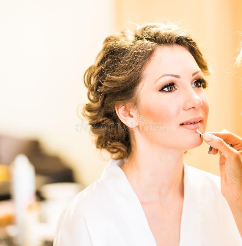 Μοντέρνη πανέμορφη νύφη που παίρνει makeup στην αίθουσα ομορφιάς στοκ φωτογραφίες