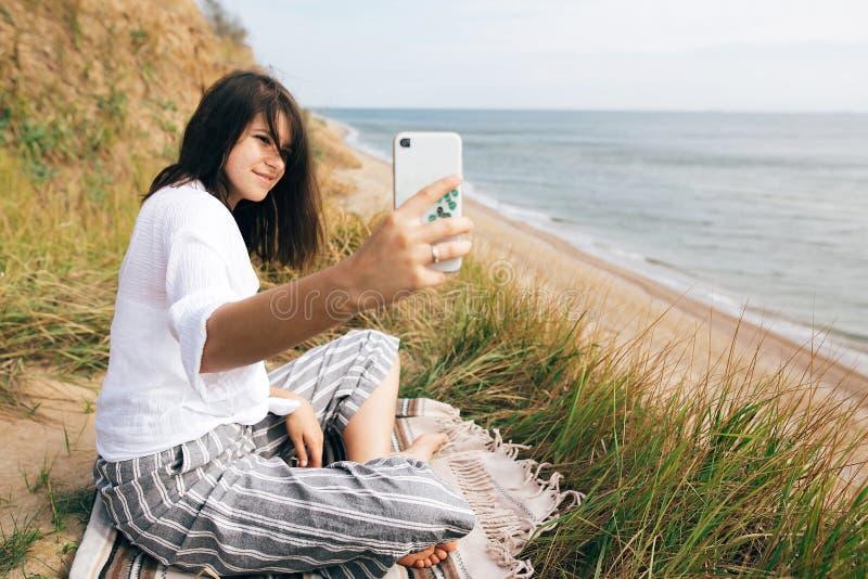 Μοντέρνη συνεδρίαση κοριτσιών hipster στο τηλέφωνο παραλιών και εκμετάλλευσης Ευτυχείς γιόγκα και περισυλλογή άσκησης γυναικών bo στοκ φωτογραφία