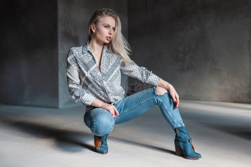 Μοντέρνη σύγχρονη νέα γυναίκα ξανθή στο μοντέρνο πουκάμισο στα καθιερώνοντα τη μόδα σχισμένα τζιν στις εκλεκτής ποιότητας μπότες  στοκ εικόνα