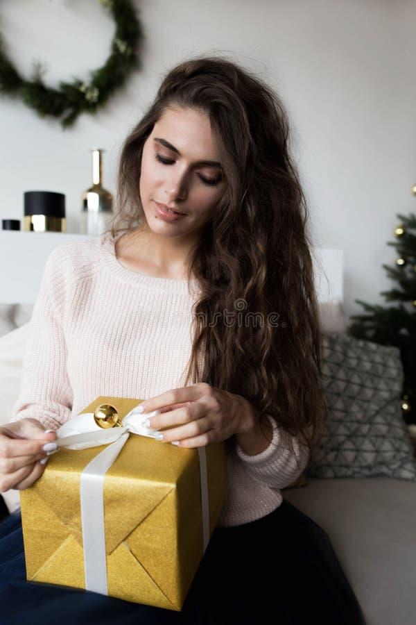 Μοντέρνη τοποθέτηση γυναικών με το χριστουγεννιάτικο δώρο στοκ φωτογραφία
