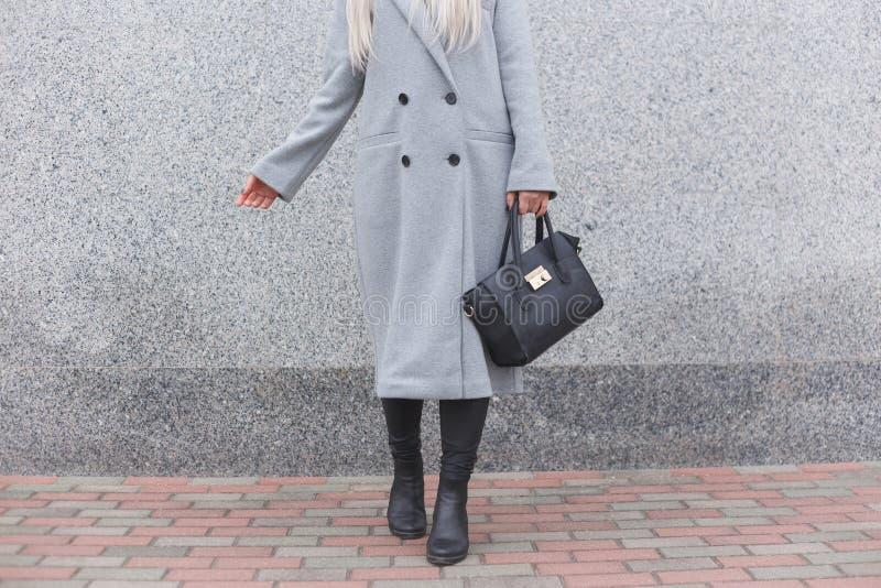 Μοντέρνη τοποθέτηση γυναικών υπαίθρια, κρατώντας τη μαύρη τσάντα δέρματος, που φορά τις μοντέρνες μπότες, κομψό παλτό Θηλυκή έννο στοκ φωτογραφία