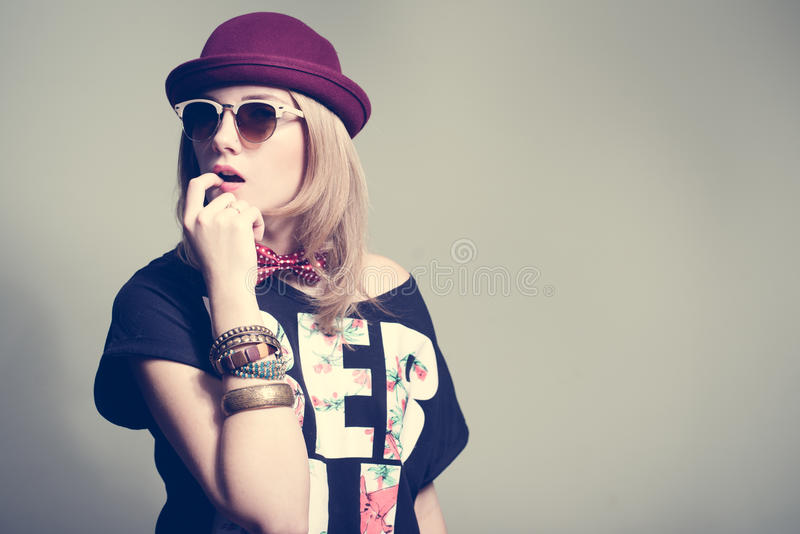 Μοντέρνη τοποθέτηση κοριτσιών hipster στο στούντιο που φορά το καπέλο στοκ εικόνα