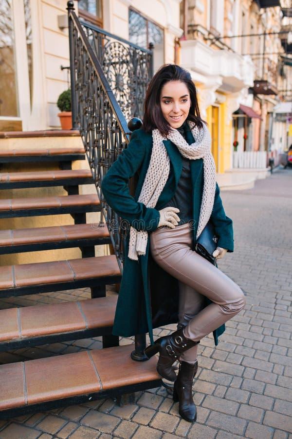 Μοντέρνη χαρούμενη νέα γυναίκα στα τακούνια κοντά στα σκαλοπάτια στην οδό Μοντέρνο μακρύ πράσινο παλτό, τρίχα brunette περικοπών, στοκ εικόνες