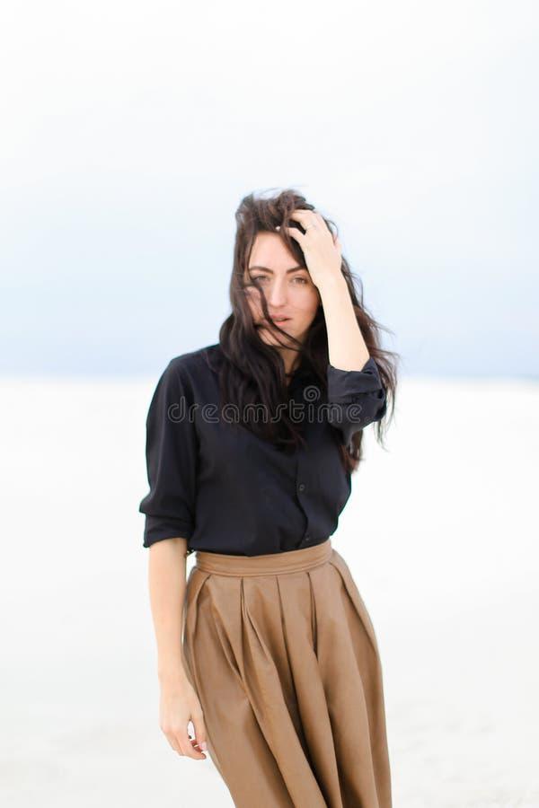 Μοντέρνη όμορφη γυναίκα που στέκεται στο χειμερινό μονοφωνικό υπόβαθρο και που φορά το μαύρο πουκάμισο με τη φούστα στοκ εικόνες