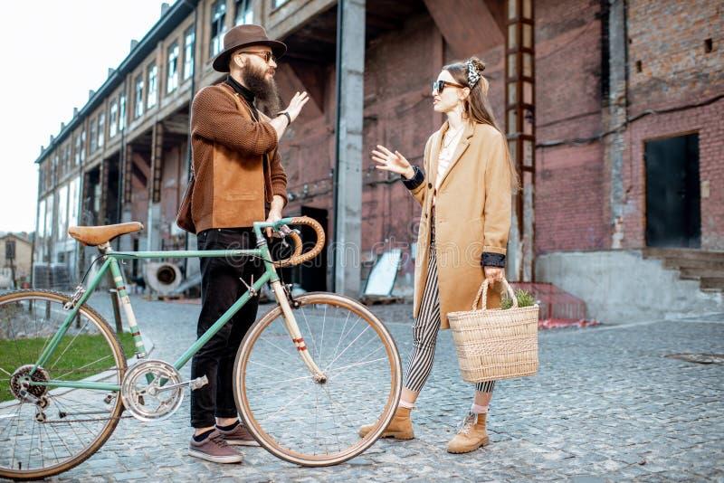 Μοντέρνοι άνδρας και γυναίκα με το αναδρομικό ποδήλατο υπαίθρια στοκ φωτογραφίες