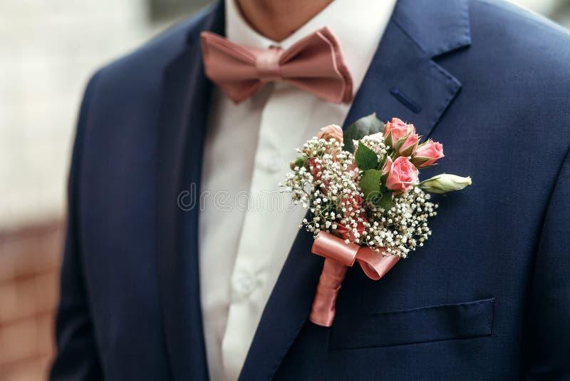 Μοντέρνοι νεόνυμφος ή groomsmen στο κοστούμι με τη ρόδινη μπουτονιέρα α τριαντάφυλλων στοκ φωτογραφία