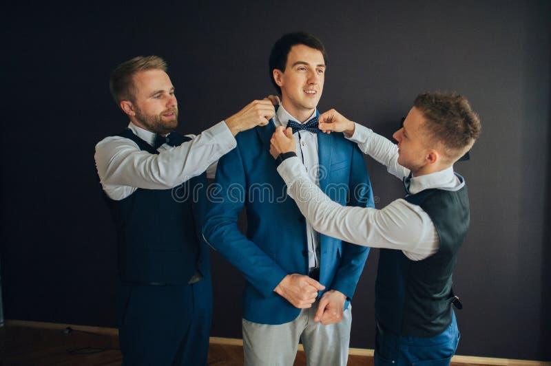 Μοντέρνοι groomsmen που βοηθούν τον ευτυχή νεόνυμφο που παίρνει έτοιμο στο morni στοκ εικόνες με δικαίωμα ελεύθερης χρήσης