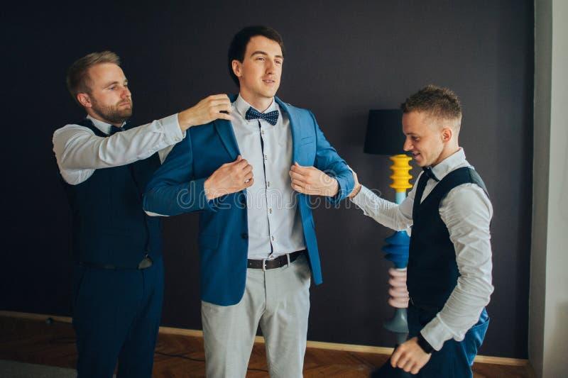 Μοντέρνοι groomsmen που βοηθούν τον ευτυχή νεόνυμφο που παίρνει έτοιμο στο morni στοκ φωτογραφία με δικαίωμα ελεύθερης χρήσης