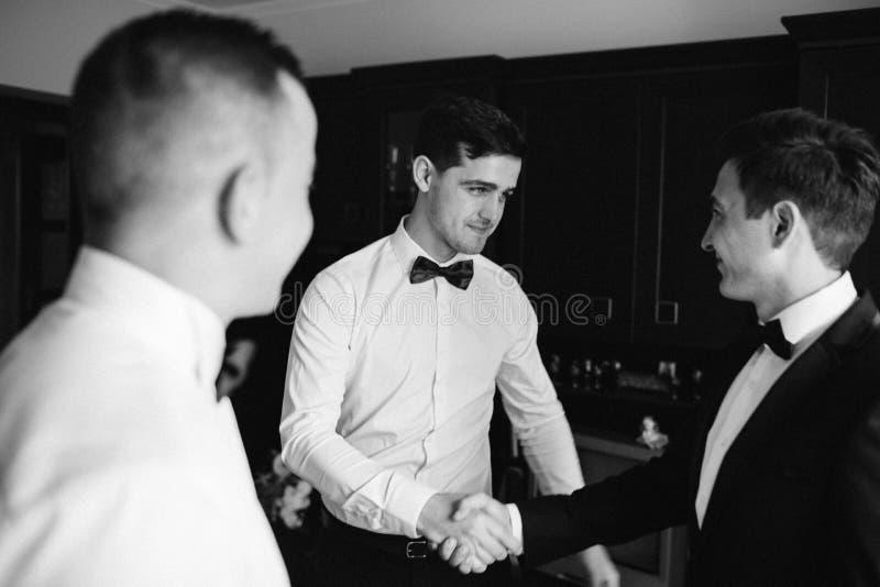 Μοντέρνοι groomsmen που βοηθούν τον ευτυχή νεόνυμφο που παίρνει έτοιμο το πρωί στοκ εικόνες με δικαίωμα ελεύθερης χρήσης