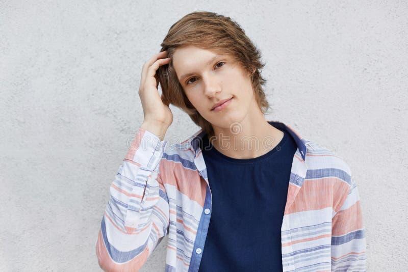 Μοντέρνος έφηβος με το σύγχρονο hairstyle που φορά απομονωμένο το πουκάμισο Ov στοκ εικόνα