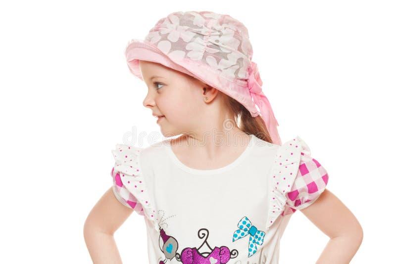 Μοντέρνος λίγο χαριτωμένο κορίτσι στο πουκάμισο και το καπέλο, που απομονώνεται στο άσπρο υπόβαθρο στοκ φωτογραφία με δικαίωμα ελεύθερης χρήσης