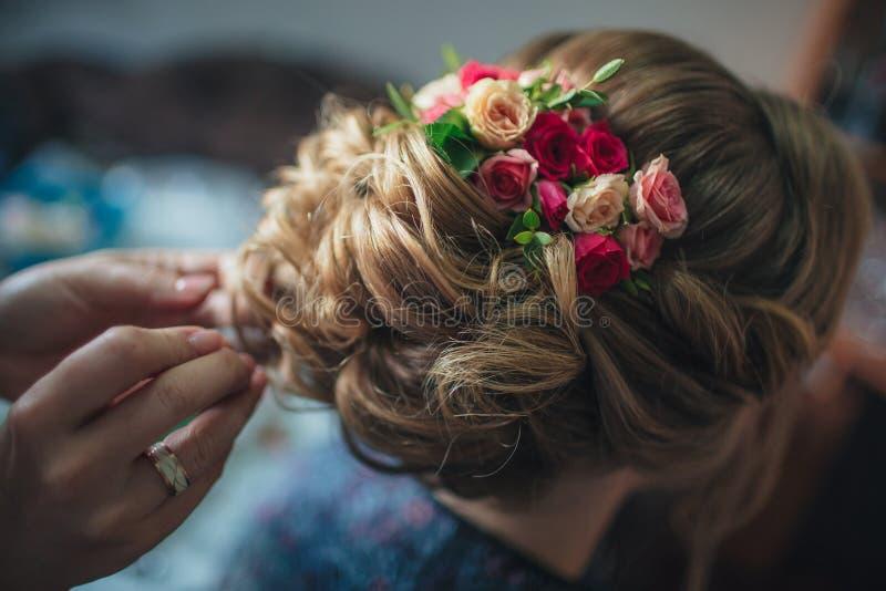 Μοντέρνος γάμος hairstyle με τα φρέσκα τριαντάφυλλα Όμορφος προσδιορισμός, οπισθοσκόπος Η νύφη στέκεται με δικούς του πίσω στη κά στοκ φωτογραφία με δικαίωμα ελεύθερης χρήσης