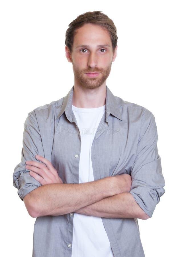 Μοντέρνος γερμανικός τύπος με τη γενειάδα και διασχισμένα όπλα στο γκρίζο πουκάμισο στοκ φωτογραφίες