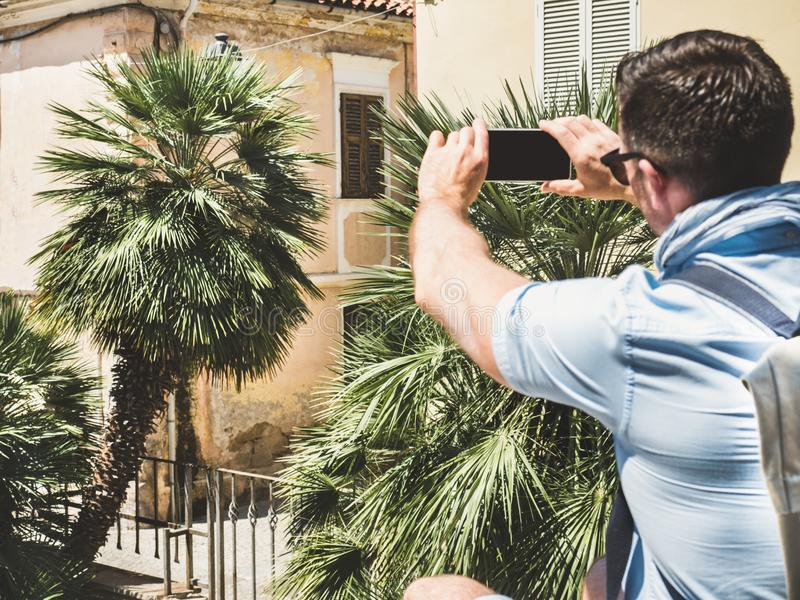 Μοντέρνος, ελκυστικός ταξιδιώτης με το smartphone που φωτογραφίζει το παλαιό κτήριο στοκ φωτογραφία