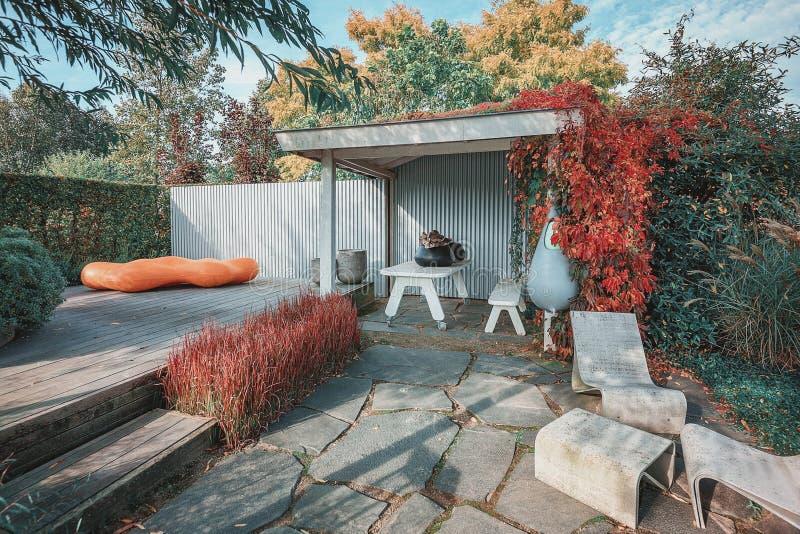 Μοντέρνος κήπος με βεράντα και προεξοχή, διακοσμημένος με μοντέρνα έπιπλα κήπου και πλανήτες σε έναν φθινοπωρινό κήπο στοκ φωτογραφία με δικαίωμα ελεύθερης χρήσης