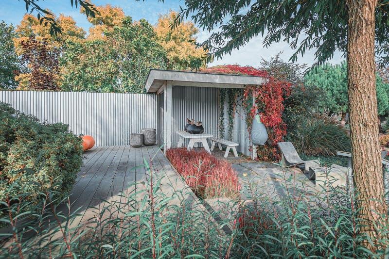 Μοντέρνος κήπος με βεράντα και προεξοχή, διακοσμημένος με μοντέρνα έπιπλα κήπου και πλανήτες στοκ εικόνες με δικαίωμα ελεύθερης χρήσης