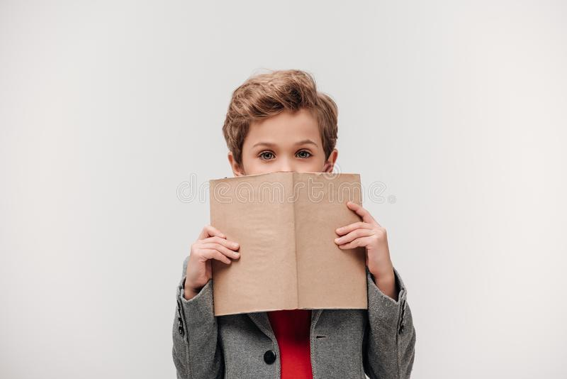 μοντέρνος λίγος μαθητής που καλύπτει το πρόσωπο με το βιβλίο στοκ φωτογραφία με δικαίωμα ελεύθερης χρήσης