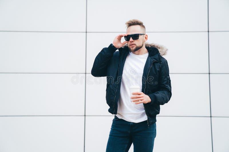 Μοντέρνος νεαρός άνδρας στο αθλητικούς σακάκι, τα γυαλιά ηλίου και τον καφέ στα χέρια του που στέκονται στο υπόβαθρο του τοίχου τ στοκ εικόνα με δικαίωμα ελεύθερης χρήσης