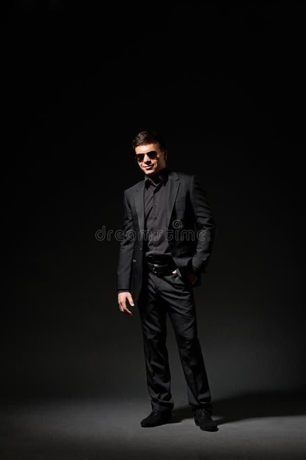 Μοντέρνος νεαρός άνδρας στο μαύρα κοστούμι και τα γυαλιά ηλίου στοκ εικόνες