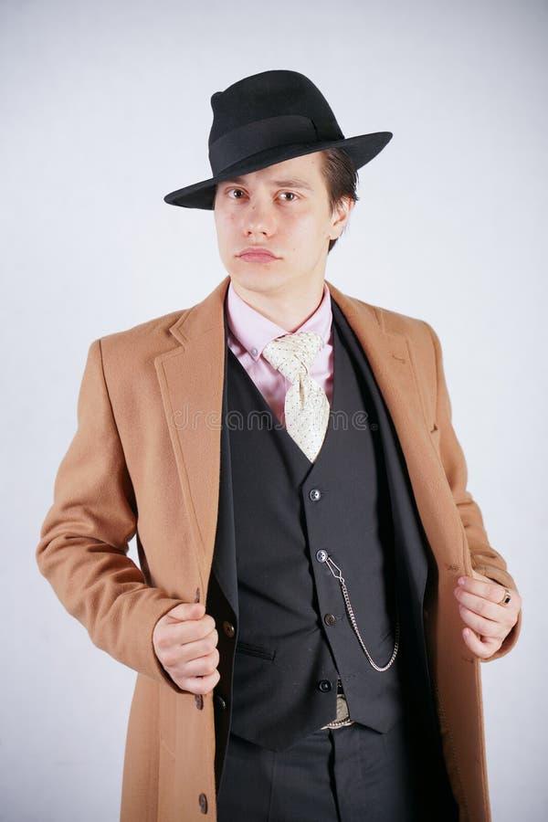 Μοντέρνος νεαρός άνδρας στο μαύρο επιχειρησιακό κοστούμι και μπεζ παλτό με το καπέλο στο άσπρο υπόβαθρο στούντιο μόνο στοκ φωτογραφίες με δικαίωμα ελεύθερης χρήσης