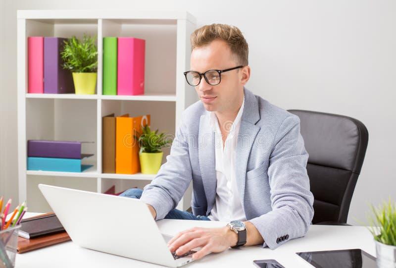 Μοντέρνος νεαρός άνδρας που εργάζεται με τον υπολογιστή στην αρχή στοκ φωτογραφία με δικαίωμα ελεύθερης χρήσης