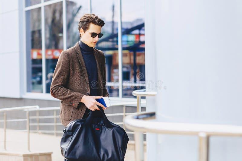 μοντέρνος ταξιδιώτης στο σακάκι με το διαβατήριο και εισιτήρια στο αστικό γ στοκ εικόνες με δικαίωμα ελεύθερης χρήσης