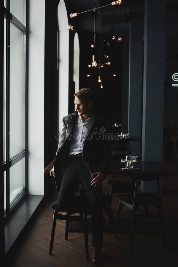 Μοντέρνος όμορφος επιχειρηματίας στο μοντέρνο παλτό στο εσωτερικό εστιατορίων στοκ εικόνα με δικαίωμα ελεύθερης χρήσης