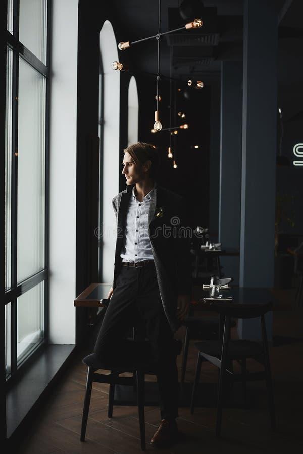 Μοντέρνος όμορφος επιχειρηματίας στο μοντέρνο παλτό στο εσωτερικό εστιατορίων στοκ εικόνα