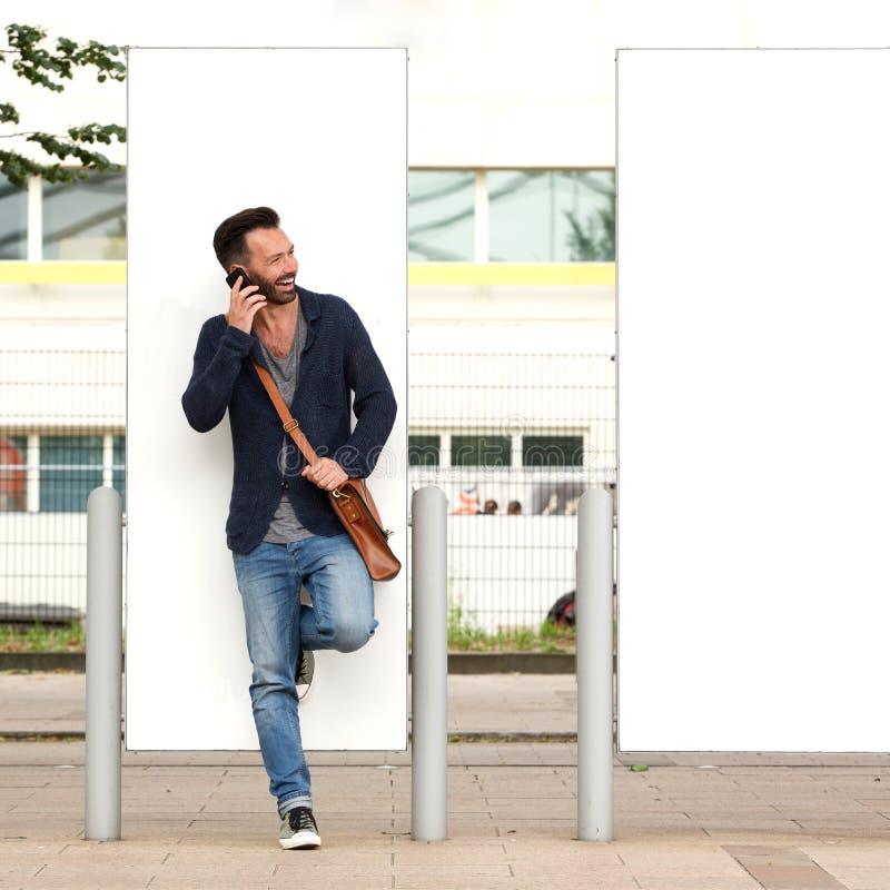 Μοντέρνος ώριμος τύπος που χρησιμοποιεί το κινητό τηλέφωνο υπαίθρια στην οδό στοκ εικόνες