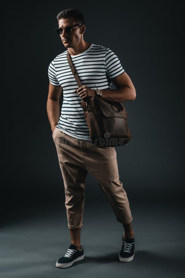 Μοντέρνο άτομο στα γυαλιά ηλίου που κρατούν την καφετιά τσάντα δέρματος και που θέτουν στο στούντιο στοκ φωτογραφίες με δικαίωμα ελεύθερης χρήσης