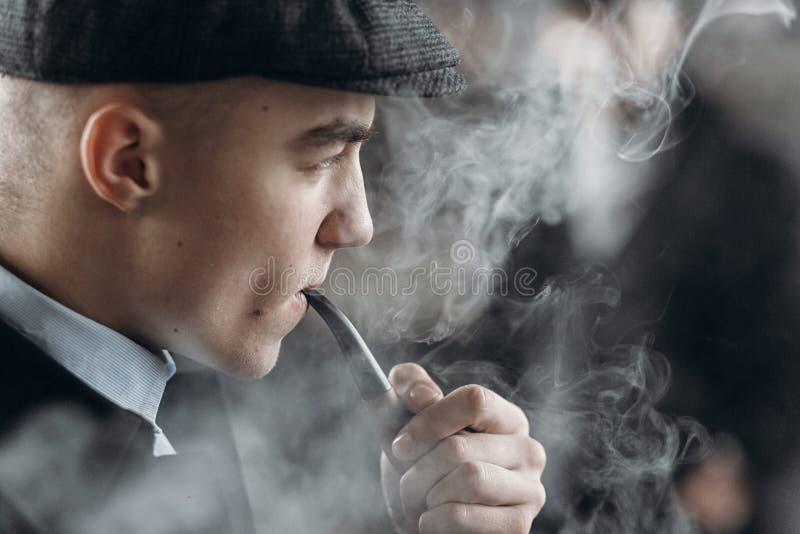 Μοντέρνο άτομο στην αναδρομική εξάρτηση, καπνίζοντας ξύλινος σωλήνας sherlock holme στοκ εικόνες