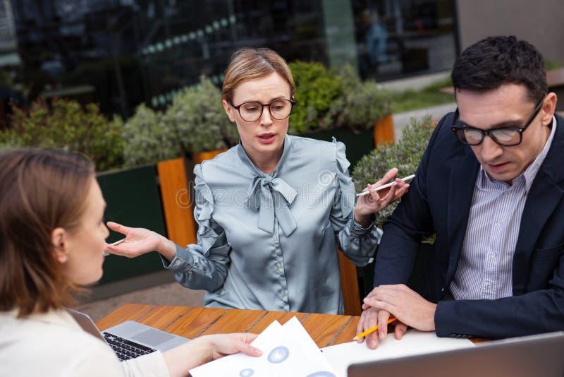 Μοντέρνο αίσθημα επιχειρηματιών που περιπλέκεται κατά τη διάρκεια της συνεδρίασης του προσωπικού στοκ φωτογραφία