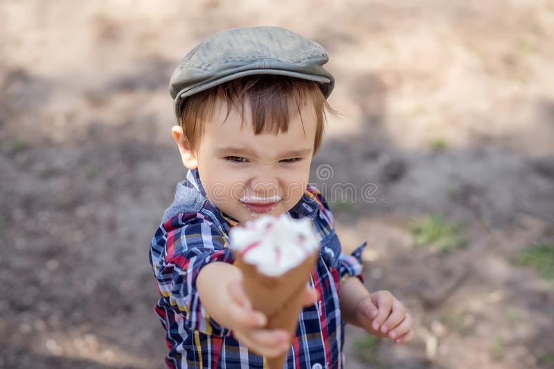 Μοντέρνο αγόρι μικρών παιδιών στο ελεγμένο πουκάμισο με το γάλα moustache που προσφέρει το παγωτό, που φθάνει έξω στο χέρι στη κά στοκ εικόνα με δικαίωμα ελεύθερης χρήσης