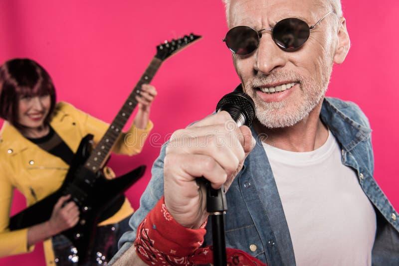 Μοντέρνο ανώτερο τραγούδι ζευγών στο μικρόφωνο και την ηλεκτρική κιθάρα παιχνιδιού στοκ φωτογραφίες με δικαίωμα ελεύθερης χρήσης