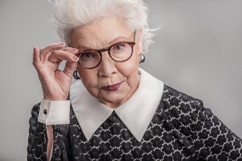 Μοντέρνο ενήλικο θηλυκό που κοιτάζει από πέρα από eyeglasses της στοκ φωτογραφίες με δικαίωμα ελεύθερης χρήσης