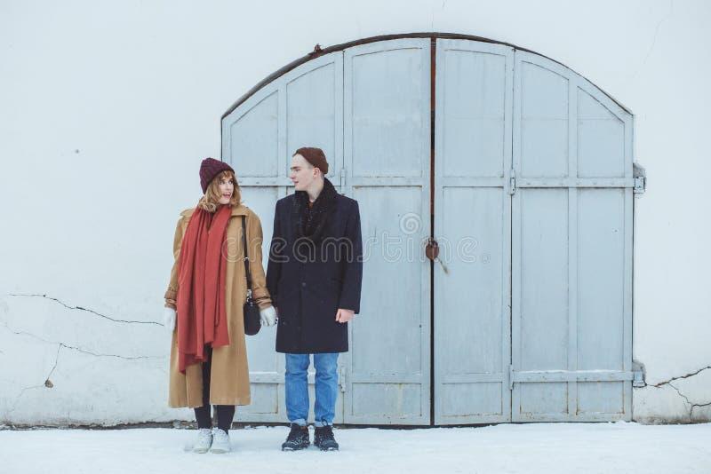 Μοντέρνο ζεύγος στην κλασική ακολουθία που στέκεται κοντά στο άσπρο ιστορικό κτήριο Μοντέρνος χειμερινός ιματισμός στοκ φωτογραφίες με δικαίωμα ελεύθερης χρήσης