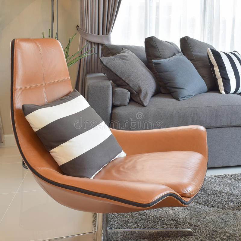 Μοντέρνο καθιστικό με το μαύρο ριγωτό μαξιλάρι στην καφετιά καρέκλα δέρματος στοκ φωτογραφίες