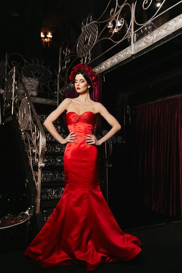 Μοντέρνο και προκλητικό λεπτό πρότυπο κορίτσι brunette με το φωτεινό makeup και με τα κόκκινα λουλούδια στο κεφάλι της στο κόκκιν στοκ φωτογραφία με δικαίωμα ελεύθερης χρήσης