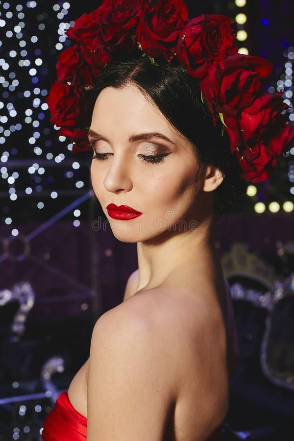 Μοντέρνο και προκλητικό λεπτό πρότυπο κορίτσι brunette με το φωτεινό makeup και με το στεφάνι των κόκκινων λουλουδιών στο κεφάλι  στοκ εικόνα