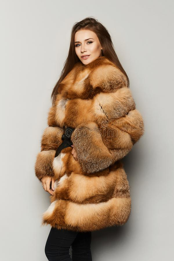 Μοντέρνο και μοντέρνο πρότυπο κορίτσι brunette με το τέλειο makeup και τα μπλε-γκρίζα μάτια, στο χρώμα πιπεροριζών παλτών γουνών  στοκ φωτογραφία με δικαίωμα ελεύθερης χρήσης